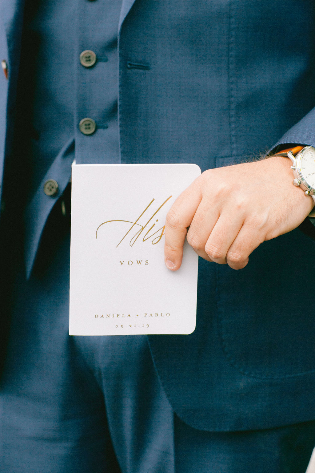 A groom holding his vow book
